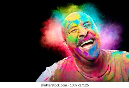 Bald cheerful man with colored face celebrating holi color festival. Man having fun with colorful powder. Closeup portrait with copy space