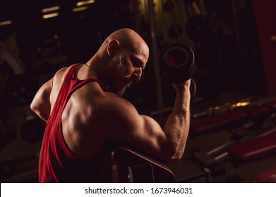 Bald cute man with a beard is doing biceps exercise. The young guy is engaged in bodybuilding. Trainer in the gym with muscular arms.