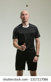 bald football referee on gray background. football referee throws a coin. the arbiter cast lots. Referee Tossing Coin on white background. the arbiter looks at the coin.