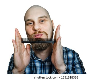 Bald funny guy with a beard and a comb in his hands, combing his head and beard in the morning at home on isolated background. Concept: humor, absurdity