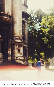 bald groom and bride brunette kissing near church on the streets of the old city Lviv Ukraine