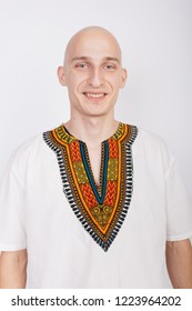 bald guy in the national African costume-dashiki. emotional portrait of a student. smiling male animator posing on white background. clothes for party and fashion show