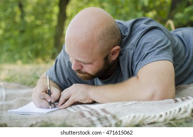 the bald guy writes to a notebook in park lying on a grass