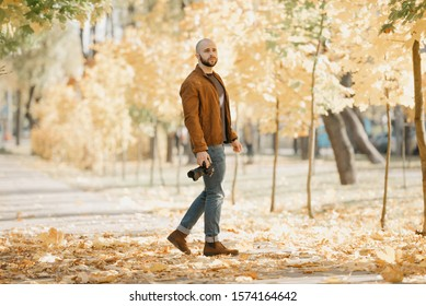 Bald half-turn photographer with a beard in a suede leather jacket, blue shirt, jeans, and Chelsea boots holds the camera and poses in the park in the afternoon