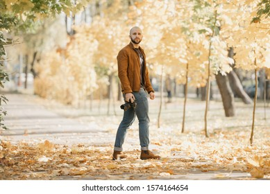 Bald half-turn photographer with a beard in a suede leather jacket, blue shirt, jeans, and Chelsea boots holds the camera and waits for a model in the park in the afternoon