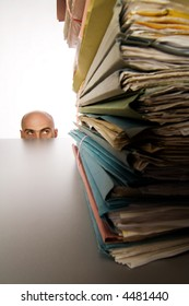 Bald head of man is visible over top of table in background.  Foreground is a stack of files.  Man appears to be hiding from or trying to avoid the work.