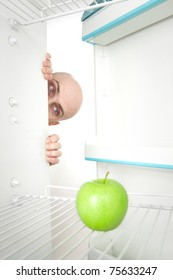Bald head of young man looking around corner of open refrigerator containing single green apple.