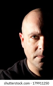 Bald headed man looking straight at the camera with half his face in deep shadow for a more dramatic image.