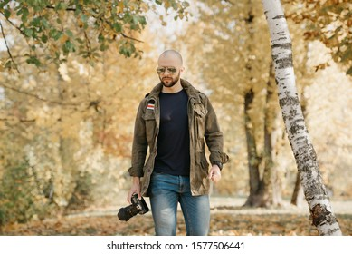 A bald journalist with a beard in aviator sunglasses with mirror lenses, olive military jacket, jeans and shirt with digital wristwatch holds the DSLR camera walks near the battlefield in the forest.