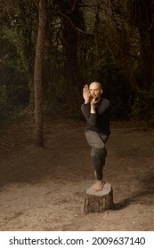 Hombre calvo latino vestido con ropa oscura, profesor de yoga practicando sobre un tronco en el bosque