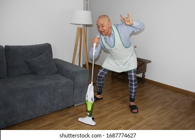 bald man at the age of 55 in home clothes and an apron is dancing happily with a vacuum cleaner, imitating playing the guitar, a cat is sitting on a sofa, a concept of household chores
