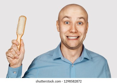 bald man with alopecia holds a comb in his hand. concept absurdity
