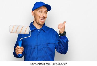 Bald man with beard holding roller painter pointing thumb up to the side smiling happy with open mouth