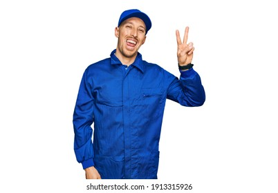 Bald man with beard wearing builder jumpsuit uniform smiling with happy face winking at the camera doing victory sign with fingers. number two.