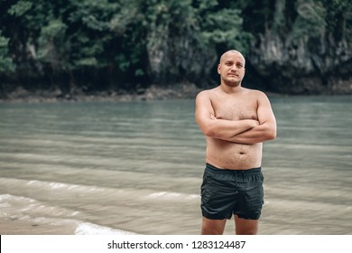 Bald man in black shorts standing by the sea. PHUKET. Thailand