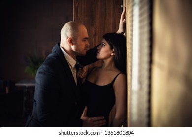 A bald man in a black suit pressed a beautiful dark-haired girl against the wall, the girl holding on to a tie. Horizontal photography