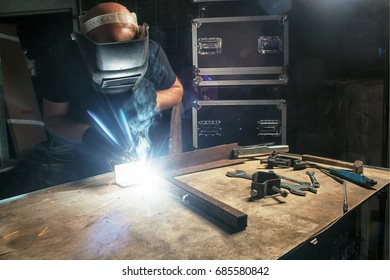 A bald man in a black T-shirt creates with his own hands a mettalical product and welds the metal with a welding machine in a dark environment, in the background metal boxes, many tools on the table