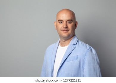 bald man in a blue jacket against a gray wall