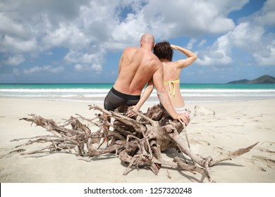 Bald man and brunette woman siting together on the wood on beautiful beach in Mexico, Caribbean sea and look at ocean.View from their back.