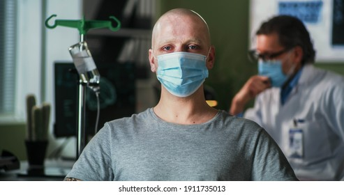 Bald man with cancer wearing mask and looking at camera while sitting near oncologist during chemotherapy session in hospital