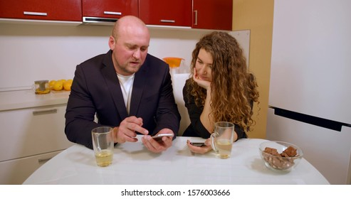 A bald man and a curly-haired girl in a jacket sit at the kitchen table and drink tea from mugs, communicate, in front of them on the table is a kettle, sweets, in their hands they hold phones.