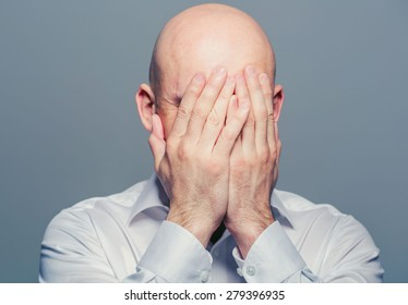 Bald man face closed hands