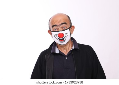Bald man with funny expression wearing a clown face protection mask