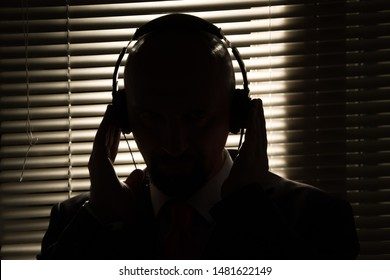 Bald man with headphones on the background of closed blinds, contour lighting, listening to music on old equipment
