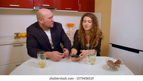 A bald man in a jacket and a curly-haired girl sit at the kitchen table and drink tea, discuss something, there is a kettle on the table in front of them, sweets, they hold phones in their hands.