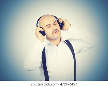 bald man with a mustache businessman listening to music on headphones and sings
