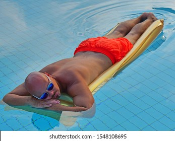 A bald man in orange swimming trunks and glasses lies on a golden mattress in a blue pool and rests