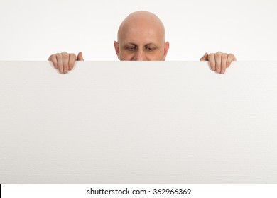Bald man peeps over top of blank white paper