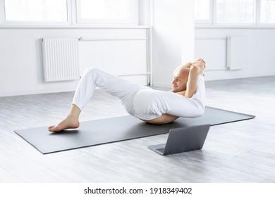 Bald man performing complex yoga pose through online instructions, young caucasian guy recording video on laptop, sit in bright modern studio, training alone. during coronavirus quarantine