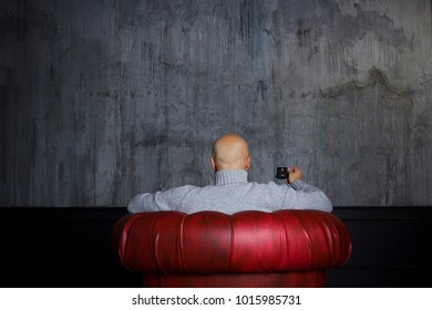 Bald man in a red chair is drinking coffee in front of a gray wall vintage