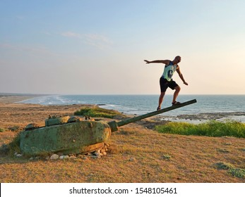 A bald man in shorts and a T-shirt climbed onto the barrel of a tank and balances against the sea