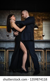 A bald man strangles a dark-haired girl in a long dress in a restaurant with his hands. Vertical photography