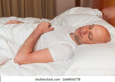 Bald man in white t shirt sleeps in a bed,