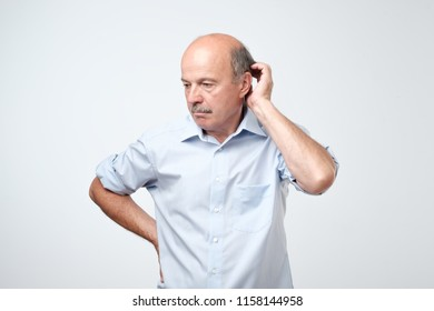 Bald mature man with mustache in blue shirt is suffering from indecision holding hands near cheeks. He do not know how to make the right decision
