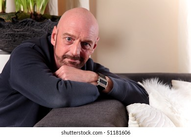 Bald Middle aged man at home relaxing on floor, artistic composition, shallow dof, focus on man.