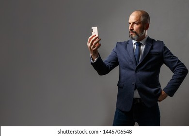 Bald middle-aged man with a beard, in a jacket with a white shirt and blue tie holding a mobile phone on a dirty gray background
