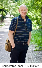 Bald middle-aged man dressed in simple dark clothes with sunglasses walks in a green park