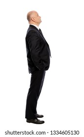Bald middle-aged man in a suit looks up, full-length, side view. Isolated on white background, vertical.