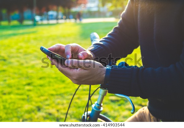 bald and millennial man on bike chatting and using smartphone at the park outdoor, technology and social networking concept