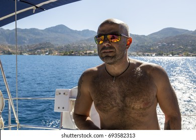 bald and naked sailor looking ahead and driving a sailing boat. Also he wears red swimming short.