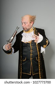 Bald old man in a 17th century costume with a vintage pistol