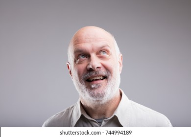 bald old man imagining beautiful good things to realize further