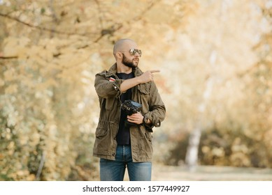Bald photographer with a beard in aviator sunglasses with mirror lenses, olive cargo combat military jacket, blue shirt with digital wristwatch holds his camera and points a finger to the right.