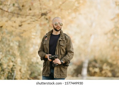Bald photographer with a beard in aviator sunglasses with mirror lenses, olive cargo combat military jacket, blue shirt with digital wristwatch holds his camera in the forest in the afternoon