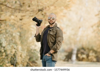 Bald photographer with a beard in aviator sunglasses with mirror lenses, olive cargo military jacket, blue jeans and shirt with digital wristwatch holds the camera in a bent hand in the forest.