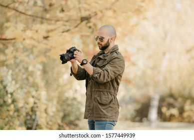 Bald photographer with a beard in aviator sunglasses with mirror lenses, olive cargo military jacket, blue jeans and shirt with digital wristwatch looking for the photo in the camera in the forest